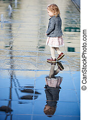 Little girl playing in street fountain