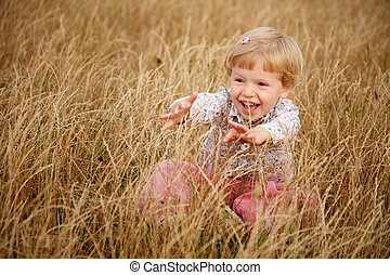 little girl playing in the grass