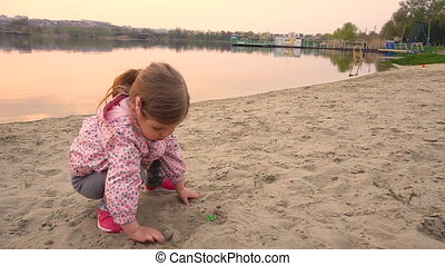 Little girl playing in the sand on beach