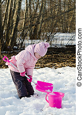 Little girl playing in the winter with snow