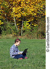 little girl playing laptop in the park autumn season