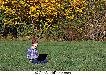 little girl playing laptop in the park