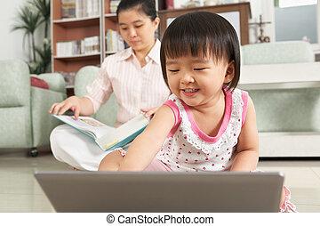 LIttle girl playing laptop