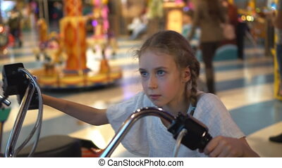 Little girl playing motorbike simulator game in theme park.