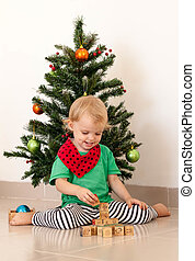 Little girl playing near the christmas tree