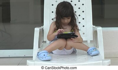 Little girl playing on computer tab