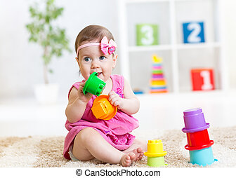 little girl playing on floor at home or kindergarten