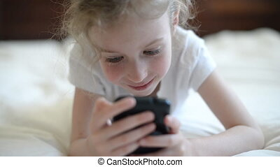 Little girl playing on mobile.
