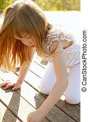 Little girl playing on park wooden floor