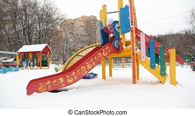 little girl playing on slide in city playground, winter