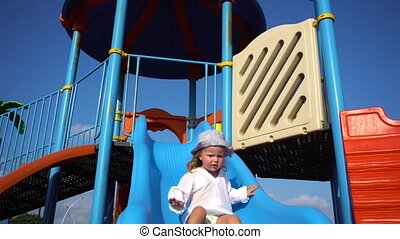 Little girl playing on slide - Sweet little girl sliding...