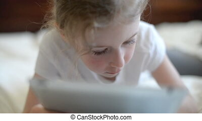 Little girl playing on tablet pc.