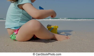 Little girl playing on the beach with her bucket