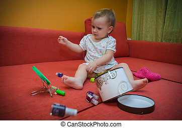 Little girl playing on the couch with makeup