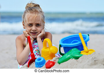 Little girl playing on the sand beach