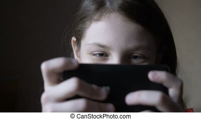 Little girl playing on the smartphone at home.