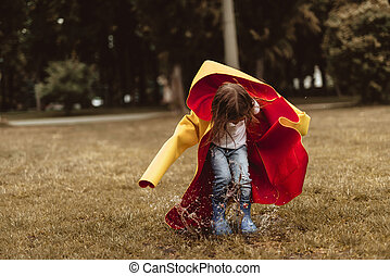 Little girl playing outside after rain