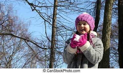 Little girl playing snowballs on a background of trees and blue sky