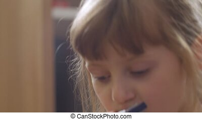 Little girl playing the harmonica home interior closeup