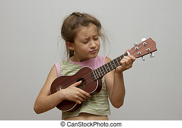 little girl playing the ukulele