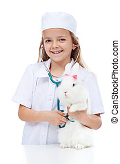 Little girl playing veterinary with her rabbit