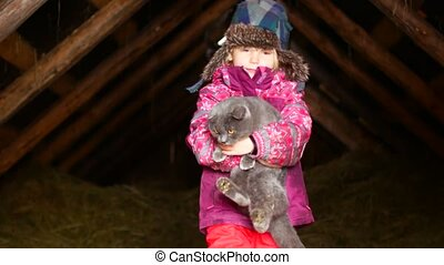 Little girl playing with a cat in winter.