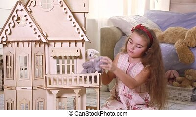 Little girl playing with a doll-house