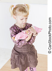 little girl playing with a doll
