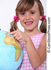 little girl playing with a globe