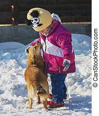 little girl playing with a mongrel dog in the snow