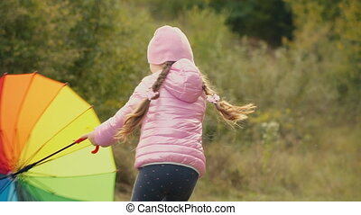 little girl playing with a multi-colored umbrella