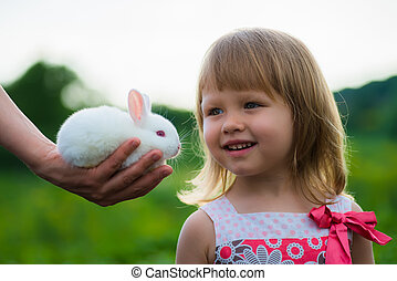 girl playing with a small rabbit