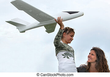little girl playing with a small scale model of plane