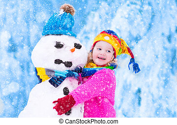 Little girl playing with a snowman - Funny little toddler...