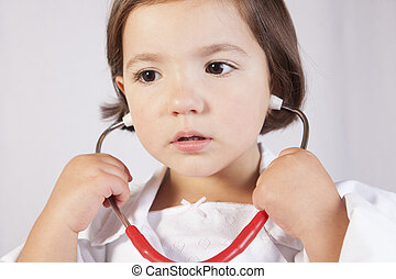 Little girl playing with a stethoscope
