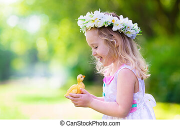 Little girl playing with a toy duck