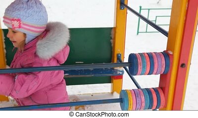 little girl playing with abacus in winter city playground