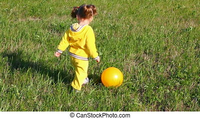 little girl playing with ball on meadow