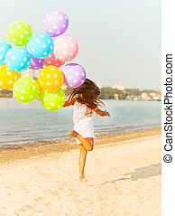 Little girl playing with balloons at the beach