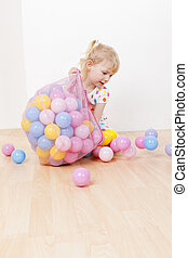 little girl playing with balls