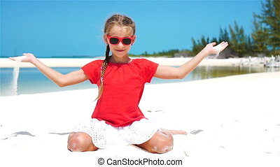 Little girl playing with beautiful white sand at tropical beach. SLOW MOTION