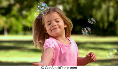 Little girl playing with bubbles in