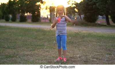 Little girl playing with bubbles in the park on a sunset