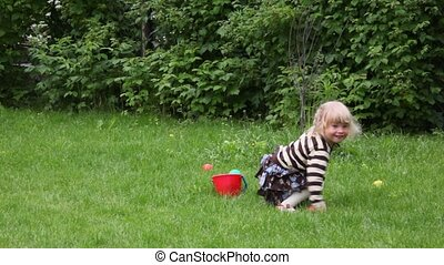 little girl playing with bucket and balls