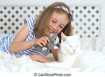 Little girl playing with cat on the bed.