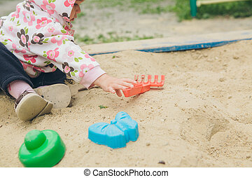 little girl playing with colorful molds in the sandbox