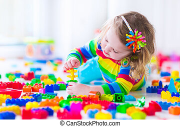 Little girl playing with colorful toy blocks - Preschooler...
