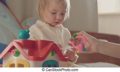 little girl playing with colorful toys on the bed of the parents .