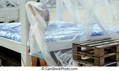 Little girl playing with curtain in bungalow on beach.