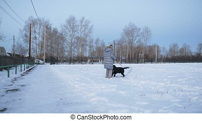 Little girl playing with dog in winter.